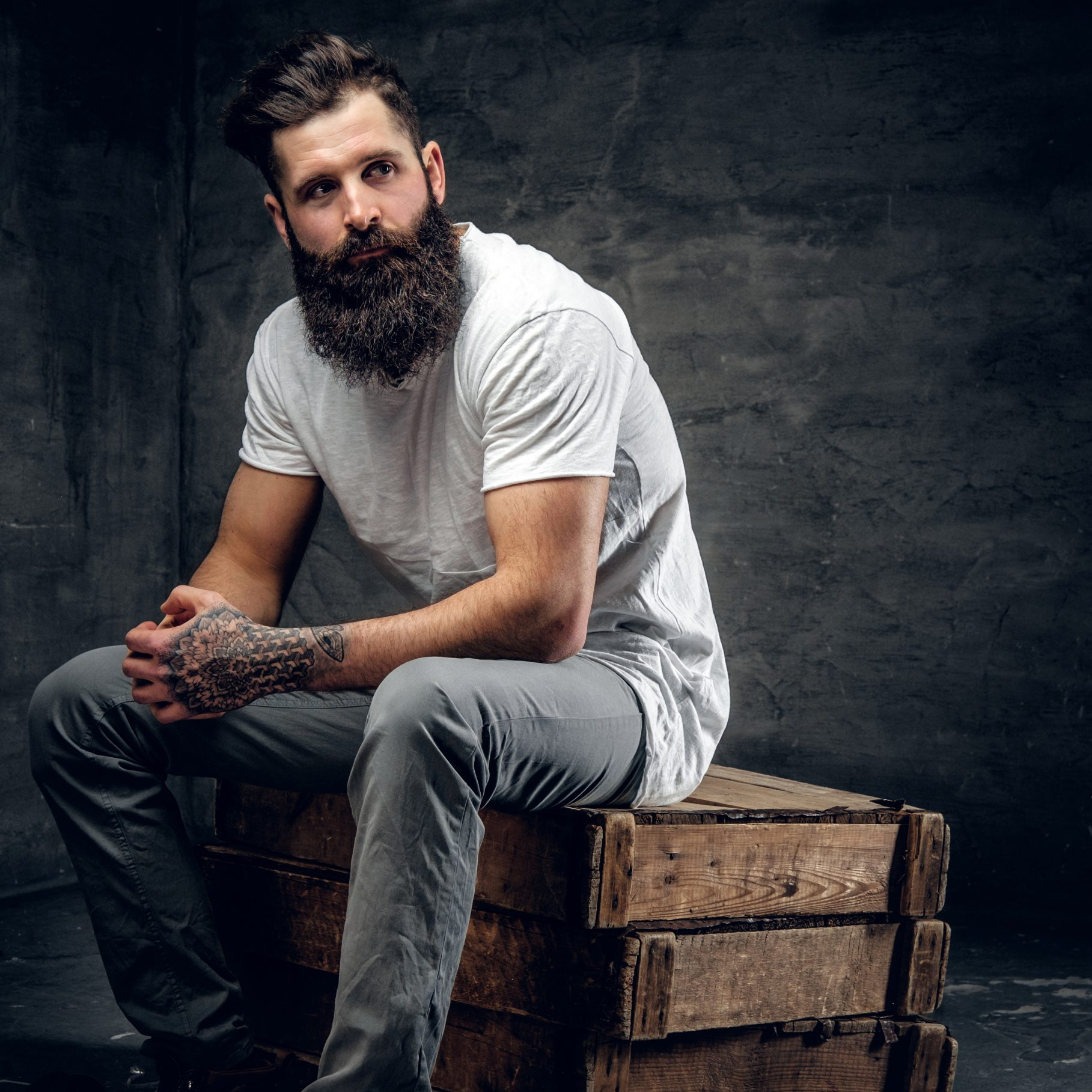 Bearded brutal male with tattoo on arm dressed in a white t shirt sits on a wooden box.